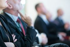 Row of business people sitting at seminar. stock photo
