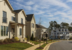 Row of upscale family homes on a curved neighborhood street. A row of upscale houses on a curved neighborhood street on a sunny day. Foreground house features a Stock Photos