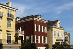 A row of upscale houses against blue sky. A row of upscale taupe, brick, and yellow houses on a partly cloudy day. Detail of balconies, shutters, cornices, and Royalty Free Stock Image