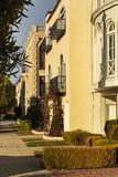 Row of upscale houses showing driveway and yard. A row of upscale yellow and beige houses showing balcony, window, driveway, sidewalk, and yard detail. Red roses Royalty Free Stock Photography