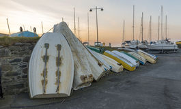 Row of upturned dinghy's, against a wall, with a background of a setting sun Stock Photo