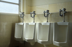 Row of Urinals. Four urinals in a row, near a window in a commercial building Royalty Free Stock Photo