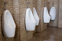Row of urinals men public toilet. Row of indoor urinals men public toilet Stock Photography