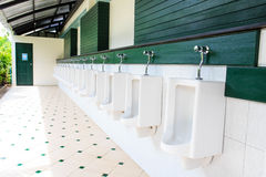 A row of urinals in tiled wall in a public restroom Royalty Free Stock Images