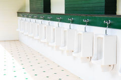 A row of urinals in tiled wall in a public restroom Stock Photography