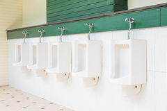 A row of urinals in tiled wall in a public restroom Royalty Free Stock Photography