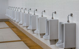 A row of urinals in tiled wall in a public restroom. Royalty Free Stock Photos