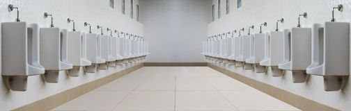 A row of urinals in tiled wall in a public restroom. A row of urinals in tiled wall in a public restroom . For the common man Stock Images