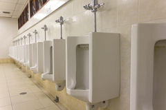 A row of urinals in tiled wall in a restroom Royalty Free Stock Photography