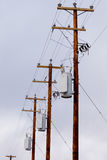 Row of utility poles power cables and transformers Royalty Free Stock Photos