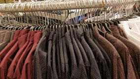Row of various fashionable men`s shirts on a huge hanger in the men`s clothing store in the shopping center. Row of various fashionable men`s shirts on a huge stock video