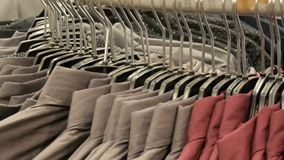 Row of various fashionable men`s shirts on a huge hanger in the men`s clothing store in the shopping center. Row of various fashionable men`s shirts on a huge stock video footage