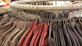 Row of various fashionable men`s shirts on a huge hanger in the men`s clothing store in the shopping center. Row of various fashionable men`s shirts on a huge stock footage