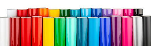 Row of various rainbow colored vinyl car wrapping or plotter cutting sticker plastic foil film rolls isolated white wide panorama