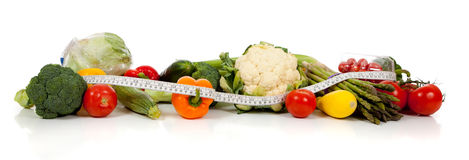 A row of vegetables and a tape measure on white Royalty Free Stock Photos