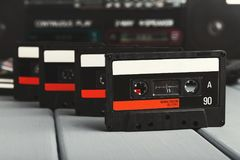 Row of vintage audio cassettes and tape recorder at gray background Stock Photo