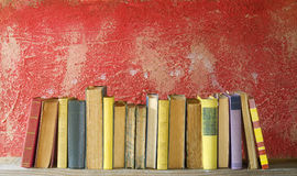 Row of vintage books on red background. Good copy space Stock Image