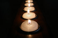 Row of Votive Candles. Long row of lit white votive candles on black background Royalty Free Stock Photos