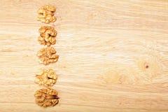 Row of walnuts on plank Royalty Free Stock Photos