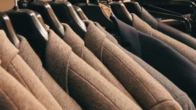A row of warm men`s jackets on a hanger at a men`s clothing store in mall. Various men`s suits hanging in the shopping. A row of warm men`s jackets on a hanger stock footage