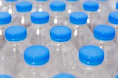 Row of water bottles. Bottles with blue caps For drinking water royalty free stock image