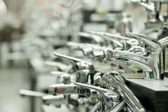 Row of water taps in building shop Stock Image