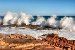 Row of wave splashes on red rock beach Stock Photography
