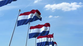 Row of waving flags of the Netherlands agaist blue sky, 3D rendering Royalty Free Stock Photo