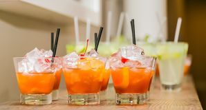 Orange cocktails on a counter at a corporate event. A row of welcome drinks on a counter top with ice and garnish Stock Photos