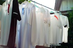 Row of wet clothes hanging on the steel rack for drying by using heat of sunlight in the traditional way. Traditional laundry drying method by using sun ray royalty free stock photography