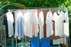 Row of wet clothes hanging on the steel rack for drying by using heat of sunlight in the traditional way. Traditional laundry drying method by using sun ray stock photo