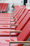 Row of Wet Red Chaise Lounge Chairs. Row of Red Chaise Lounges in the Rain stock photos
