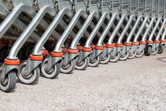 Row of wheels of metal shopping carts stock photos