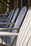 A Row of White Adirondack Chairs. A row of rustic Adirondack chairs on a porch of a wooden lodge Royalty Free Stock Images