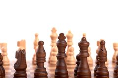 Row of white and black wooden chess pieces on a chessboard, isolated on white background. Row of white and black wooden chess pieces on a chessboard, with stock photos
