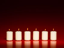 Row of white burning candles. Closeup of a group of white burning candles in a row on red background Royalty Free Stock Images