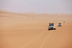 Row of white cars in desert. Row of white off-road cars in african desert Royalty Free Stock Photo