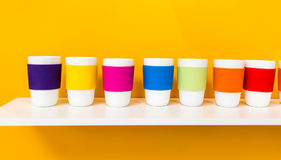 Row of white ceramic cup with colorful pantone silicone cup. Holder on white shelf against yellow background. Minimal concept for decoration Royalty Free Stock Images