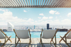 Row of white chairs near a pool in a city Royalty Free Stock Photography
