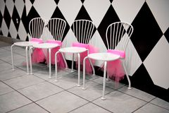 Row of White Chairs with Pink Ribbons. A row of four white chairs with pink bunting or ribbons tied around them next to a black and white wall Royalty Free Stock Photos