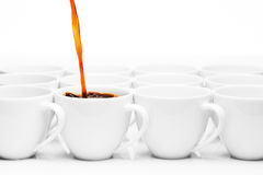 Row of white coffee cups, one being filled with coffee Stock Photos