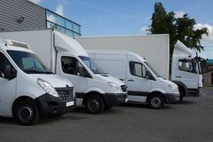 Row of white delivery and service van, trucks and cars in front of a factory and warehouse. Distribution plant Stock Photo