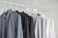 Row of white, gray, black shirts hanging in wooden wardrobe Stock Photography