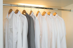 Row of white and grey shirts in white wardrobe Stock Photos