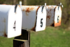 A row of white mailboxes. A set of mailboxes with the numbers four, five, and six on them Stock Photography