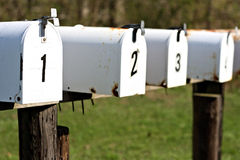 A row of white mailboxes. A set of mailboxes with the numbers one, two, and three on them Royalty Free Stock Images