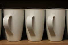 A Row White Mugs sat on a shelf Stock Photo