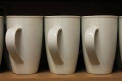 A Row White Mugs sat on a shelf Stock Photo