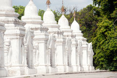 Row of white pagodas in Kuthodaw temple,Myanmar. Stock Photos