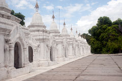 Row of white pagodas in Kuthodaw temple,Myanmar. Stock Image